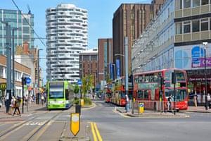 Croydon town centre with London double decker bus & tram public transport services & the No.1 Croydon NLA Tower landmark beyond