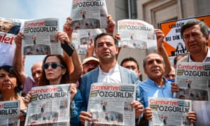 People hold copies of today's Cumhuriyet daily newspaper on July 28, 2017 during a demonstration in front of Istanbul's courthouse