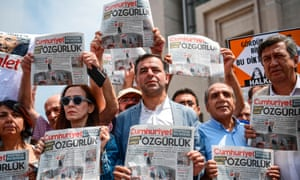 Protesters hold copies of the Cumhuriyet newspaper
