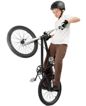 Young boy performing trick on BMX bicycle