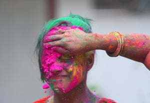 A girl is covered in powder by her friends in Agartala, the capital of the north-eastern state of Tripura