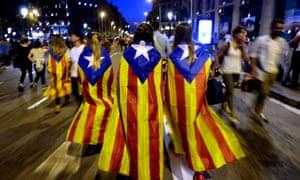 Catalan people wearing pro-independence 'Estelada' regional flags