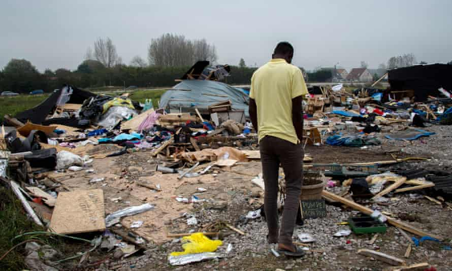 A man walks past debris in the Calais camp as the clearance enters its final stage.