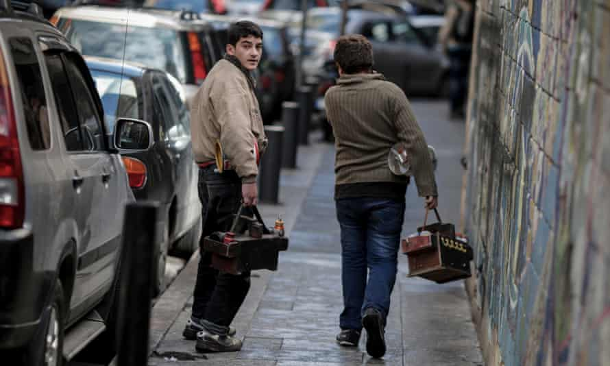 Young Syrian refugees look for shoe-shine clients in Beirut.