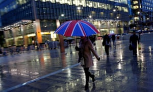 City workers walk in the rain in London's Canary Wharf.