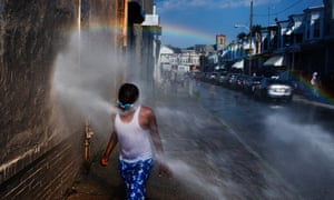 A fire hydrant sprays a child in Philadelphia, which with Baltimore shares the highest rate of deaths due to hot weather in the US.