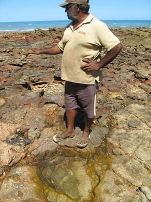 Goolarabooloo elder Phillip Roe stands in front of a dinosaur footprint near James Price Point, north of Broome, Western Australia.