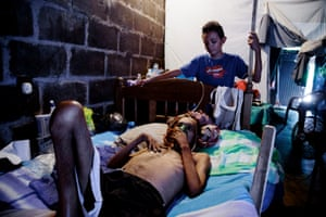 Former sugar cane worker Don Julio Lopez lies in a hospital bed with his son watching over him