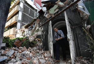A man walks out of the door frame of a building that collapsed after an earthquake, in the Condesa neighborhood of Mexico City, Tuesday, Sept. 19, 2017.