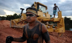 Two Amazon Indians stand near a heavy machinery being used in the construction of the massive Belo Monte hydroelectric dam during a 2012 protest.