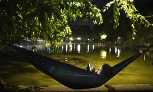 A woman relaxes in a hammock by the Cismigiu lake on a hot evening in Bucharest, Romania