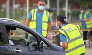 Workers in NHS test and trace jackets at a Covid-19 testing centre in Bolton, north-west England