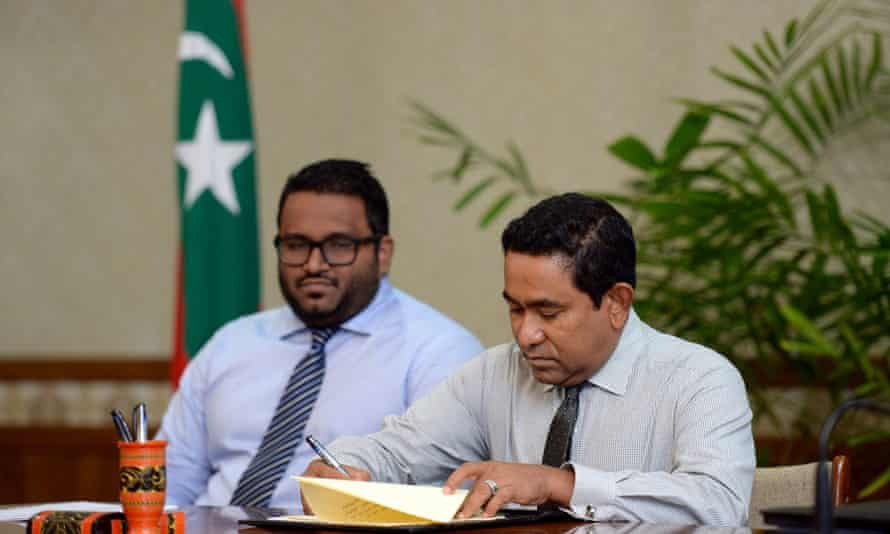 The Maldivian president, Abdulla Yameen, ratifies the law allowing foreign ownership of land for the first time, watched by the vice-president, Ahmed Adeeb. India is concerned at Beijing's growing influence in an area it regards as its backyard.