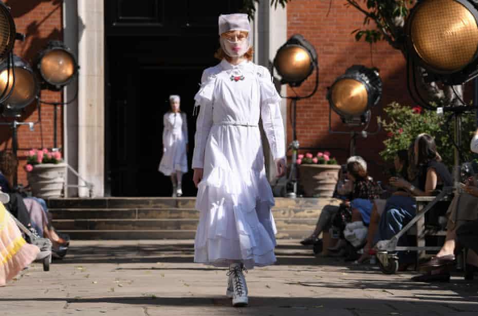 A model in head-to-toe white dress, with gauze mask, at Bora Aksu's fashion show