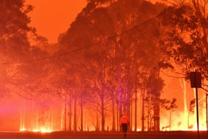 A firefighter battles the bushfires around the town of Nowra, New South Wales.