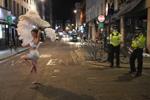London, England Police officers look on as an entertainer walks past in Soho. Pubs, cafes and restaurants will have to shut at 10pm every night under new measures to control the rising rate of coronavirus