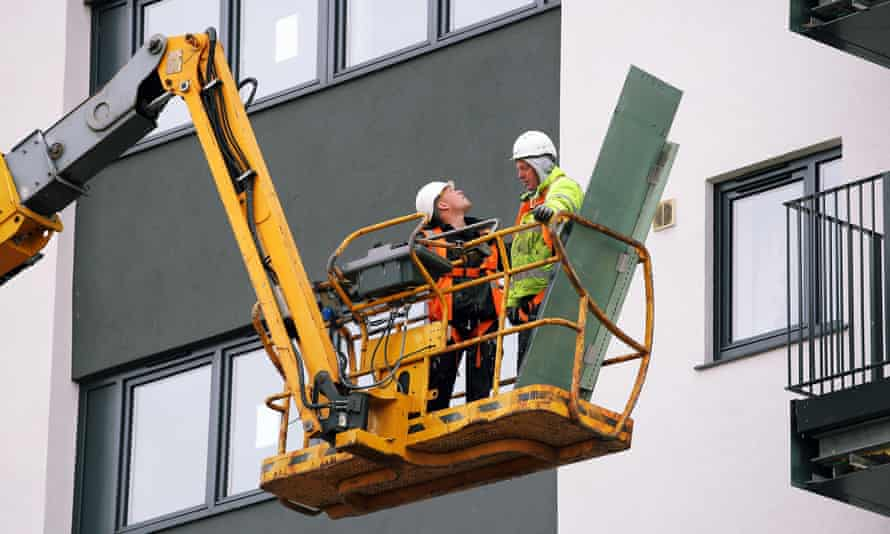 Workers on a cherry picker lift remove cladding panels from flats.