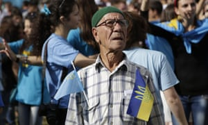 A man carries flags of Crimean Tatars and Ukraine while celebrating the Day of Crimean Tatars National Flag in Simferopol, in 2014