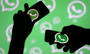 Two people holding smartphones in front of the WhatsApp logo.