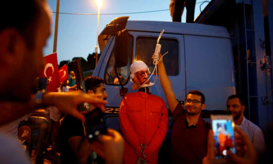 Man holding up noose around neck of effigy of cleric