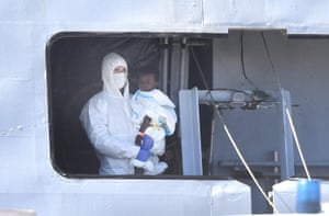 A medical worker helps a baby disembark from an Italian navy ship in Genoa, Italy