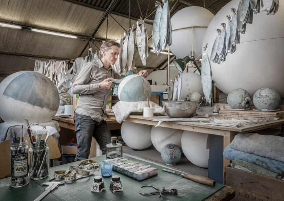A globe-maker surrounded by spheres and the tools of the trade.