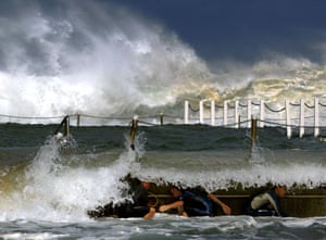 Young boys crouch behind an ocean pool wall as they play in the massive surf at Sydney's Narrabeen beach.