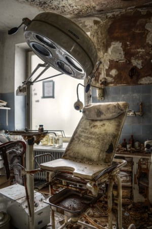 A treatment chair covered with mould in a room with peeling walls and debris on the floor.