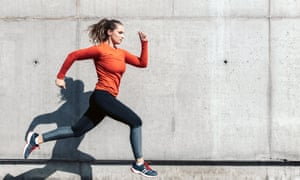 young sportswoman running outdoors<br>Posed by model young sportswoman in red sports dress running outdoors in front of concrete wall
