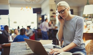 Businesswoman talking on phone and using laptop in cafe.