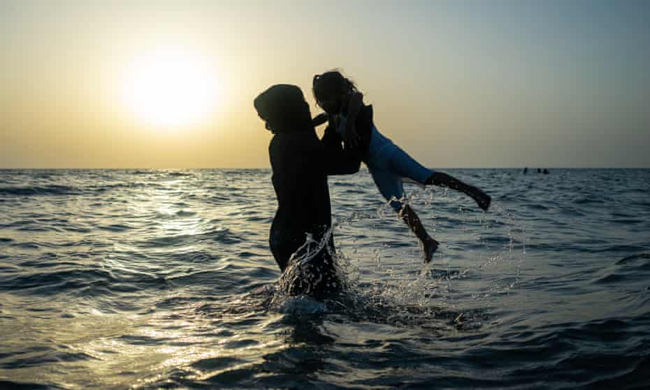 A Yemeni mother of four plays with one of her children in the Red Sea, near Hodeidah.