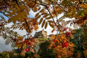 Edinburgh Castle is framed by trees displaying their autumn colours in Princes Street gardens.