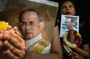 Women pray while holding an image of the late Thai king, Bhumibol Adulyadej.