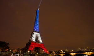 The Eiffel Tower is lit with the blue, white and red colours of the French flag