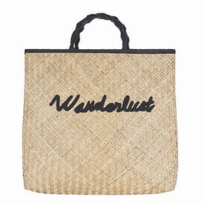woven raffia bag with black handles and black 'wanderlust' slogan