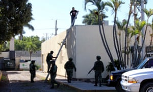 Soldiers stand guard where the body of a man, who witnesses said was tossed from a plane, landed on a hospital roof in Mexico's Sinaloa state.