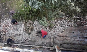 People work on the outer wall of a house that collapsed in an earthquake in Imphal.
