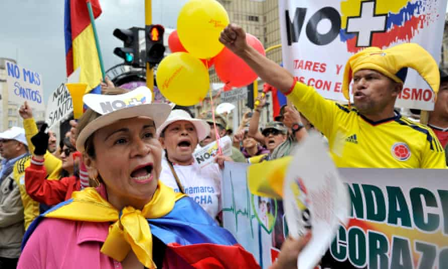 People take part in a march against the government of president Juan Manuel Santos and Farc guerrillas. Colombia is trying to implement peace deals with the country's two leftist guerrilla groups, Farc and ELN.