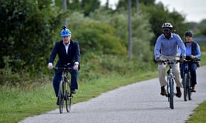 Boris Johnson (left) and and Darren Henry, the Conservative MP for Broxtowe (centre), riding bikes at the Canal Side Heritage Centre in Beeston earlier today.