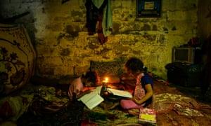 Palestinian children do their homework during a power cut in Gaza