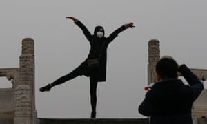 A woman wearing a protective mask poses for photo