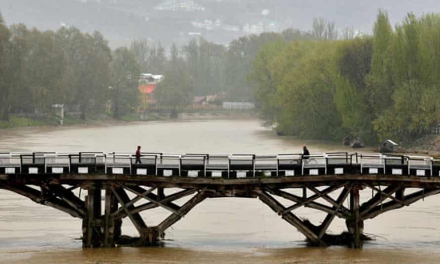 People cross a bridge at the River Jhelum