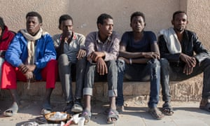 Men from Ethiopia and Somalia sit by the roadside in Ataq, Shabwa Province, Yemen.