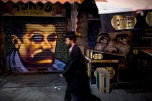 An ultraorthodox Jewish man walks past a portrait