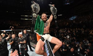 Conor McGregor celebrates with his two title belts at UFC 205