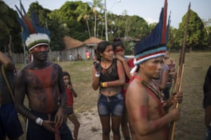 People gather for a meeting of the Tembe tribes in the Tekohaw village, in Para state, Brazil. Under a thatch-roof shelter in the Amazon rainforest, warriors wielding bows and arrows, elderly chieftains in face paint and nursing mothers gathered to debate a plan that some hope will hold at bay the loggers and other invaders threatening the tribes of the Tembe