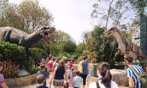 Dinosaur models and visitors at a Gulliver's Valley theme park.