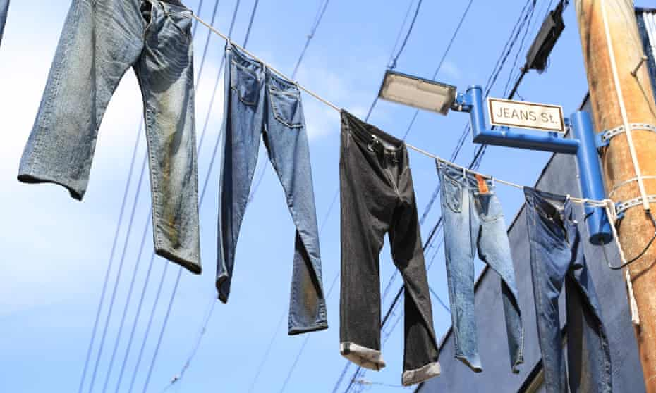 Five pairs of Jeans hanging on washing lines across a street.