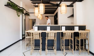 Michal Kubiak behind the counter, with bamboo high seats around it, in a clean white dining room