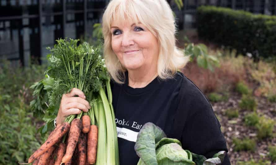 Liz Grant holding up a bunch of carrots and other vegetables
